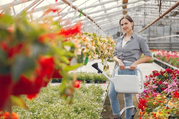 Vrouw in een blauw shirt giet bloempotten