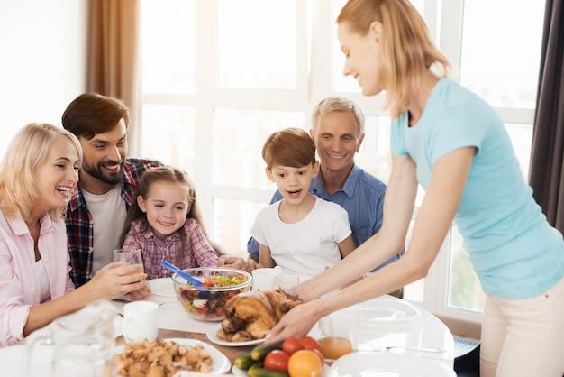 Vrouw in een blauw t-shirt geeft de gebakken kalkoen aan tafel.