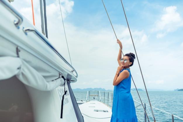 Vrouw in een blauwe jurk die zich op een jacht bevindt