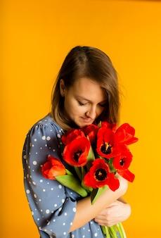 Vrouw in een blauwe jurk houdt rode tulpen vast en ruikt bloemen op een gele muur