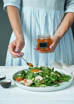 Vrouw in een blauwe jurk voegt saus toe aan een bord met salade. koken concept.