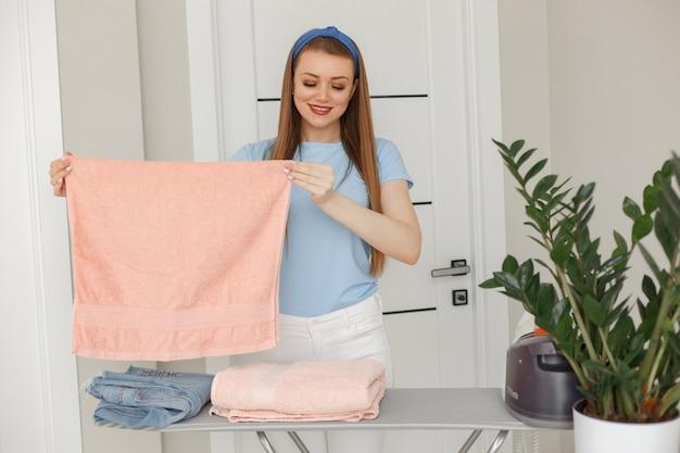 Vrouw in een blauwe t-shirt die thuis strijken