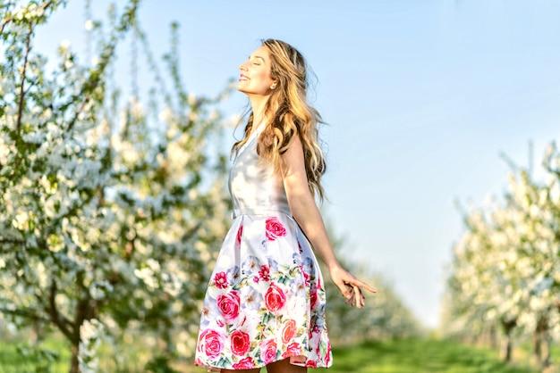 Vrouw in een bloeiende kersenboomgaard in de lente