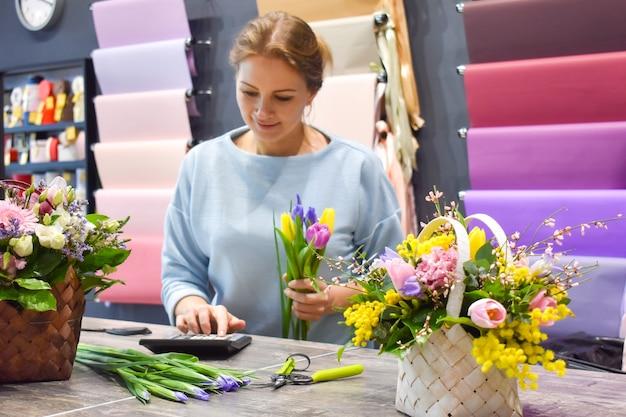 Vrouw in een bloemenwinkel die bloem maakt.