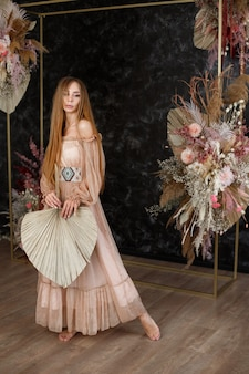 Vrouw in een boho-jurk in de buurt van de bloemencompositie