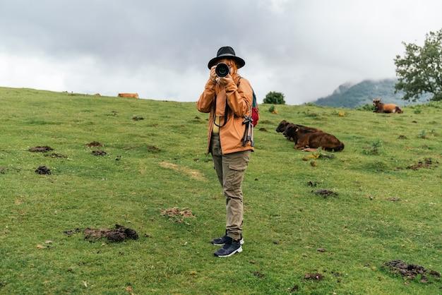 Vrouw in een bruine jas die een foto maakt in een veld met de bewolkte lucht met koeien op de achtergrond