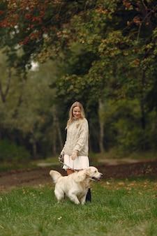 Vrouw in een bruine trui. dame met een labrador. vrienden hebben plezier buiten.