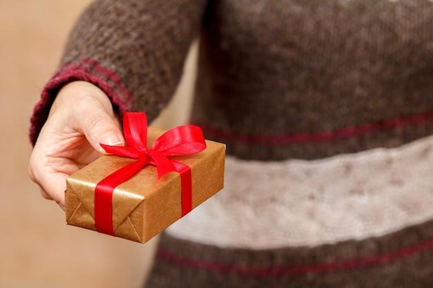 Vrouw in een bruine trui met een geschenkdoos vastgebonden met een rood lint in haar hand. ondiepe scherptediepte, selectieve focus op de doos. concept van het geven van een cadeau op vakantie of verjaardag.