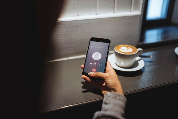 Vrouw in een café die op haar telefoon praat