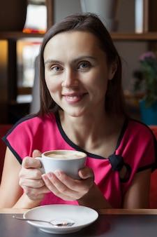Vrouw in een café houdt een kopje koffie in haar handen en glimlacht