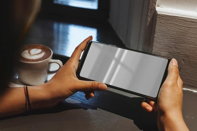 Vrouw in een café met een mobiele telefoon