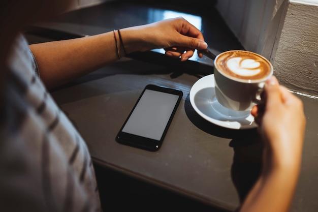 Vrouw in een café nippend van haar koffie