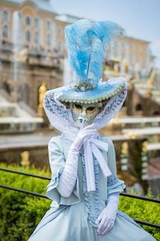Vrouw in een carnavalmasker en in een blauwe jurk tegen de ruimte van fonteinen op een zonnige dag