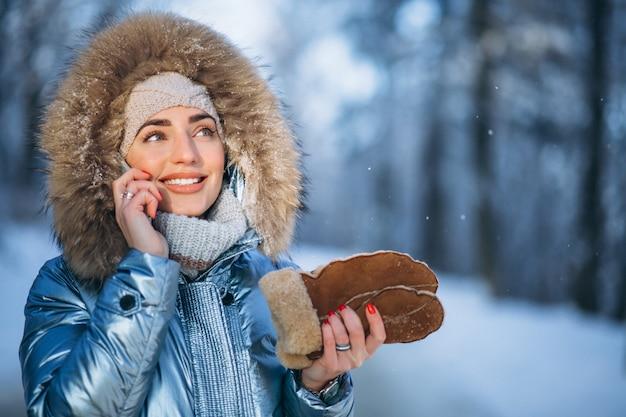 Vrouw in een de winterpark die op de telefoon spreken