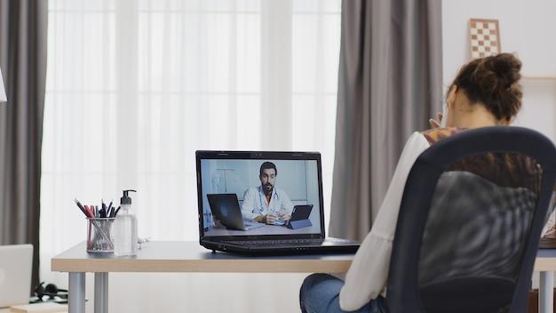 Vrouw in een extern videogesprek met haar arts die tabletcomputer gebruikt.