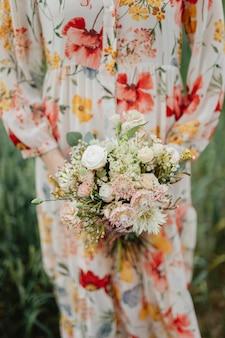 Vrouw in een gebloemde jurk met een bloemboeket
