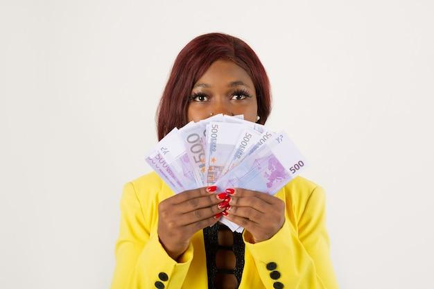 Vrouw in een geel jasje met eurorekeningen in haar handen