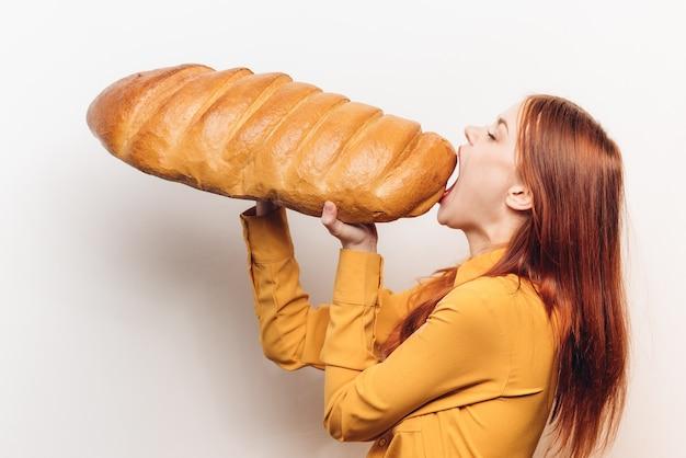 Vrouw in een geel overhemd met een enorm brood in haar handen een lichte achtergrond van het meelproduct. hoge kwaliteit foto