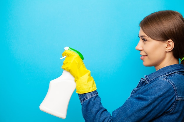 Vrouw in een gele handschoen houdt een spray van reinigingsvloeistof op een blauwe achtergrond.