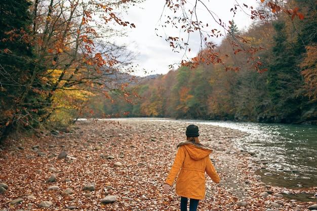 Vrouw in een gele jas in de buurt van de natuur van rivierbergen
