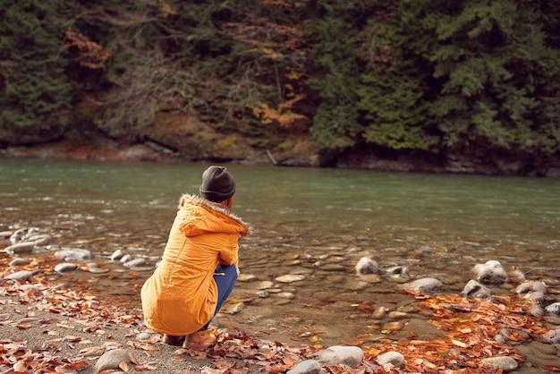 Vrouw in een gele jas in de buurt van de rivier bewondert natuur herfst bos
