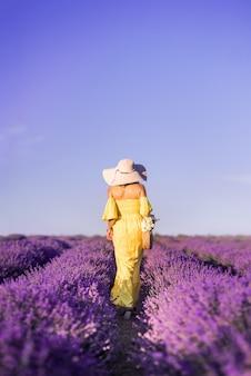 Vrouw in een gele jurk en hoed loopt in een veld met lavendel. uitzicht vanaf de achterkant. prachtig lavendelveld en blauwe lucht