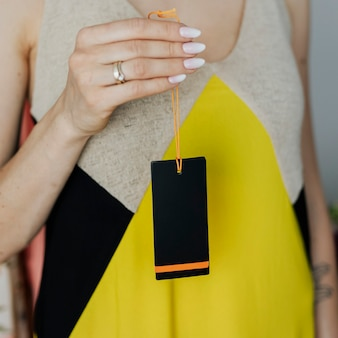 Vrouw in een gele jurk met een zwart stoffen merklabel