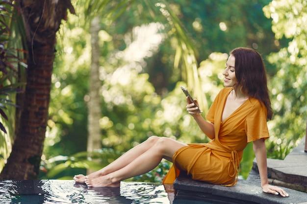 Vrouw in een gele jurk zitten bij het zwembad op een bali
