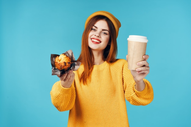 Vrouw in een gele trui en pet met een kopje koffie cupcake in haar handen een snack