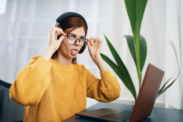 Vrouw in een gele trui voor een laptop thuis werkt freelance
