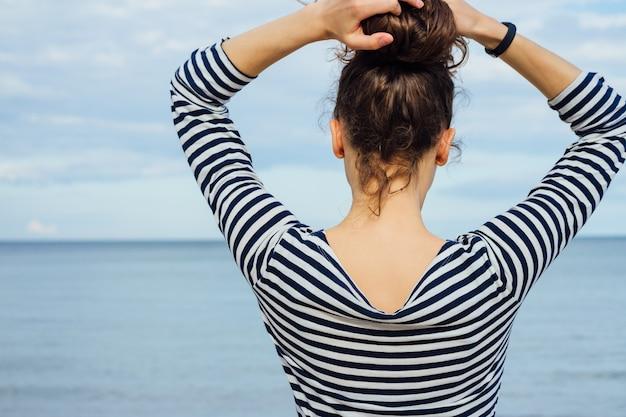 Vrouw in een gestreept overhemd die het overzees bekijken