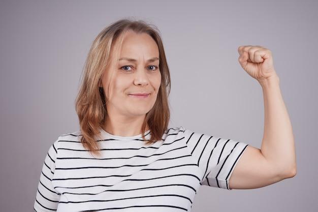 Vrouw in een gestreept overhemd toont biceps op haar arm
