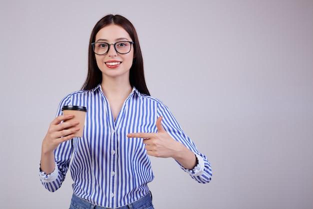 Vrouw in een gestreept shirt en zwarte pc-bril staat met een bruine kop koffie in haar hand op grijs. de dame kijkt kalm recht. glimlach.