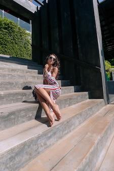 Vrouw in een gestreepte jurk poseren buitenshuis