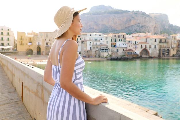 Vrouw in een gestreepte zomerjurk met hoed genieten van uitzicht op cefalu, badplaats, sicilië, italië Premium Foto