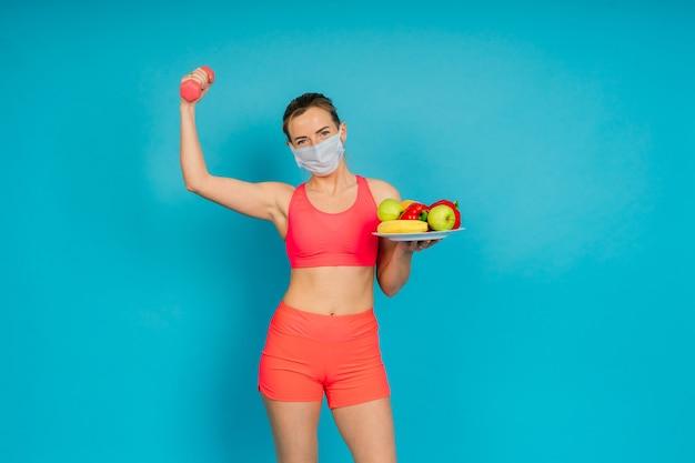 Vrouw in een gezichtsbeschermingsmasker en fitnessslijtage geïsoleerd over blauwe achtergrond.