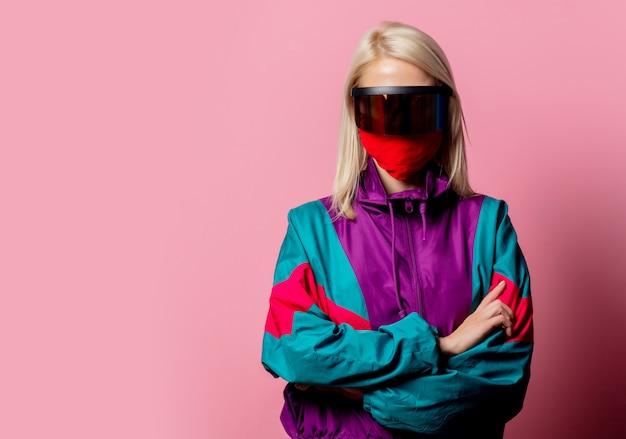 Vrouw in een gezichtsmasker en 3d-bril op roze
