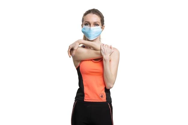 Vrouw in een gezichtsmasker en een oranje sportkostuum die tijdens de quarantaine trainen