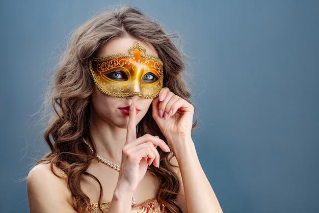 Vrouw in een gouden jurk en carnaval masker op een blauwe achtergrond haar vinger aan haar lippen te raken