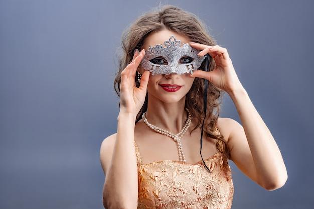 Vrouw in een gouden jurk en parelketting draagt een glanzend carnaval masker