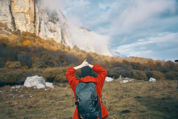 Vrouw in een grijze hoed rode jas met een rugzak gebaren met haar handen op de natuur in de bergen