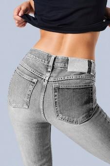 Vrouw in een grijze spijkerbroek met een tag