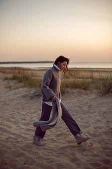 Vrouw in een grijze trui en broek komt met een sjaal op het strand in laarzen bij zonsondergang bij het gras
