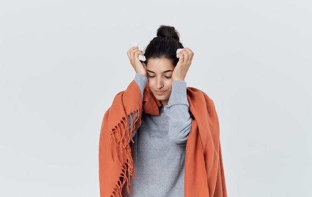 Vrouw in een grijze trui met een rode plaid op haar schouders portret copy space gezondheidsproblemen. hoge kwaliteit foto