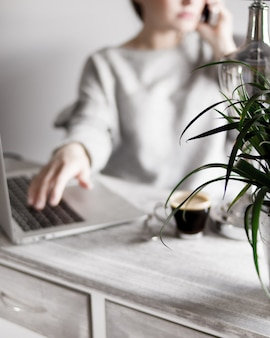 Vrouw in een grijze trui praten aan de telefoon met haar hand op een laptop en koffie op tafel
