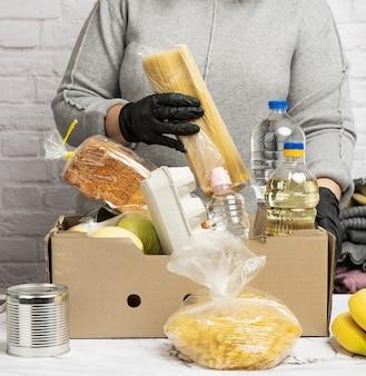 Vrouw in een grijze trui verpakt voedsel in een kartonnen doos, het concept van hulp en vrijwilligerswerk, donatie