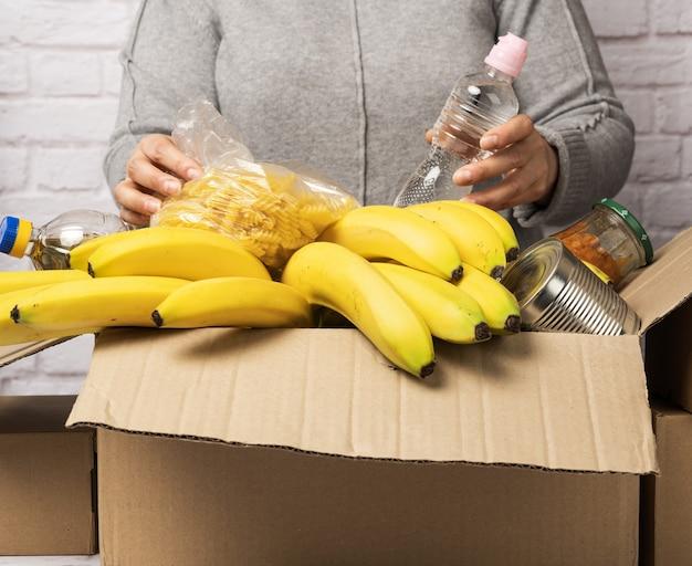Vrouw in een grijze trui zet in een kartonnen doos verschillende soorten voedsel, fruit, pasta, zonnebloemolie in een plastic fles en conserven. donatie en vrijwilligerswerk concept