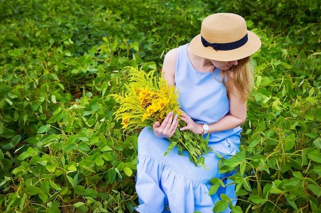 Vrouw in een groen veld zit met een boeket wilde bloemen