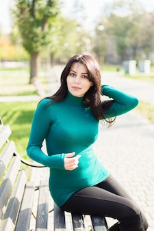 Vrouw in een groene trui zittend op een bankje