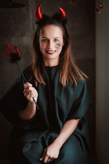 Vrouw in een heksenkostuum en skeletmake-up opent een zwart spreukenboek voor een heks op halloween.